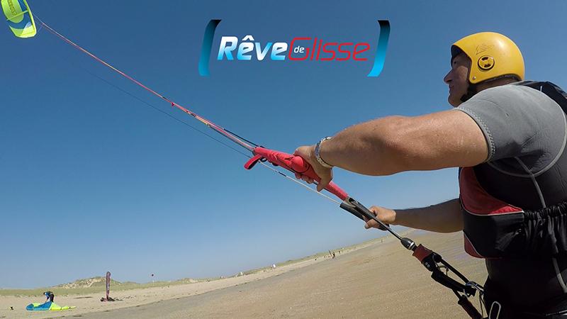Stage kitesurf Morbihan. Pilotage d'une aile de kite à l'école kitesurf Quiberon Rêve de Glisse. Cours de kitesurf débutant sur la plage. L'élève pilote son aile. Il porte tout l'équipement dont le casque et le gilet pour aller naviguer dans la mer.
